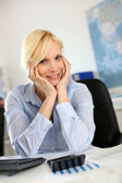 Businesswoman at desk with hands on chin — Stock Photo