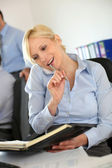 Businesswoman on the phone writing on agenda — Stockfoto