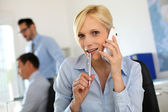 Businesswoman on the phone taking note on agenda — Stock Photo