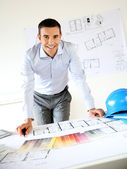 Smiling architect leaning on desk in office — Stock Photo
