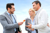 Salesman giving home keys to property owners — Stock Photo