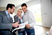 Middle-aged couple visiting house with salesman — Stock Photo