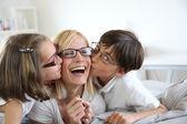 Portrait of children kissing her mom — Stock Photo