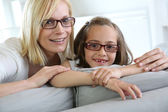 Mom and little girl sitting in sofa — Stock Photo
