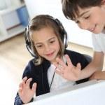 Retratos de niños saludando webcamera con portátil — Foto de Stock