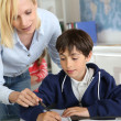 Teacher helping young boy with lesson — Stock Photo #27880111