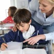 Teacher helping young boy with lesson — Stock Photo