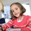 Portrait of beautiful little girl in class — Stock Photo #27880167