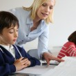 Teacher looking at classbook with young boy — Stock Photo #27880173