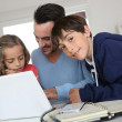 Man with children using laptop at home — Stock Photo #27880199