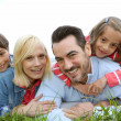 Family of four relaxing in countryside — Stock Photo
