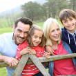 Family leaning on a fence in countryside — Stock Photo #27880329