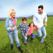 Family of four running together in natural landscape — Stock Photo