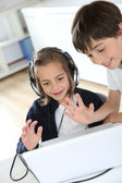 Portrait of kids waving at webcamera with laptop — Stock Photo