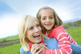 Woman holding daughter on her back — Stock Photo