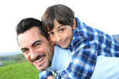 Man holding son on his back — Stock Photo