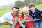 Family leaning on a fence in countryside — Stock Photo