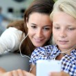 Stock Photo: Teenager and woman listening to music with smartphone