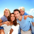Parents giving piggyback ride to kids at the beach — Stock Photo