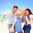Happy couple with kids at the beach — Stock Photo