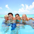 Family of four bathing in swimming pool — Stock Photo