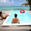 Family hanging around infinity pool by the sea — Stock Photo