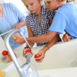 Kids washing fresh tomatoes for salad — Stock Photo