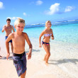 Family running on paradisaical beach — Stock fotografie #27917735