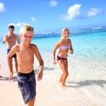 Family running on a paradisaical beach — Stock Photo