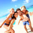 Family of four having fun at the beach — Stock Photo