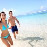 Couple running on a sandy beach — Stock Photo