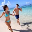 Couple running on a sandy beach — Stock Photo
