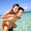 Man giving piggyback ride to girlfreind in Caribbean sea — Stock Photo