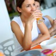 Brunette girl enjoying orange juice for breakfast — Stock Photo