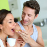 Cheerful couple enjoying breakfast time — Stock Photo #27917989