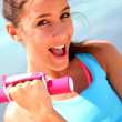 Cheerful girl lifting weights — Stock Photo