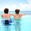 Couple looking at the sea from swimming-pool — Stock Photo