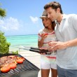 Cheerful couple in holidays preparing grilled meat — Stock Photo