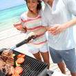 Cheerful couple in holidays preparing grilled meat — Stock Photo #27918137