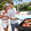 Cheerful couple in holidays preparing grilled meat — Stock Photo #27918147