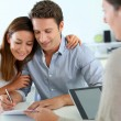 Couple signing real-estate contract — Stock Photo #27918255
