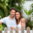 Couple leaning on fence in front of home — Stock Photo