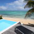 Infinity pool with deck chair by the beach — Stock Photo #27918513