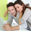 Cheerful couple looking at internet on tablet — Stock Photo