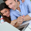 Stock Photo: Couple at home sitting in front of laptop