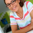 Cheerful girl with eyeglasses working on laptop — Stock Photo