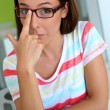 Stock Photo: Girl putting her eyeglasses up