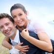 Groom giving pigguback ride to bride — Stock Photo