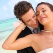 Just married couple standing on a paradisiacal beach — Foto Stock