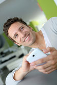 Smiling man in couch using telephone — Stock Photo